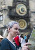 Kobieta ogląda mapę miasto na tle dziejowy średniowieczny astronomiczny zegar na Starym urzędzie miasta w Praga, czech Ponowny zdjęcia stock