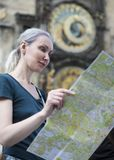 Kobieta ogląda mapę miasto na tle dziejowy średniowieczny astronomiczny zegar na Starym urzędzie miasta w Praga, czech Ponowny fotografia stock
