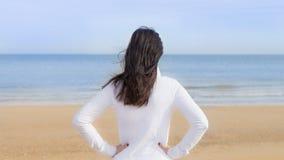 Kobieta ogląda morze, jej ręki na jej biodrach, widzieć od plecy Fotografia Royalty Free