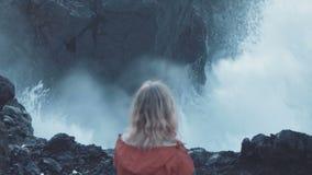 Kobieta ogląda ogromną fala na oceanu brzeg zbiory