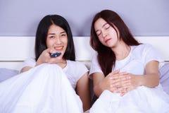 Kobieta ogląda telewizję podczas gdy jej przyjaciel śpi na łóżku Obrazy Stock