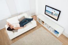 Kobieta ogląda tv podczas gdy kłamający na kanapie obraz stock