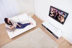 Kobieta ogląda tv podczas gdy relaksujący na kanapie obrazy stock
