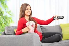 Kobieta ogląda tv sadzającego na kanapie w domu Zdjęcia Royalty Free