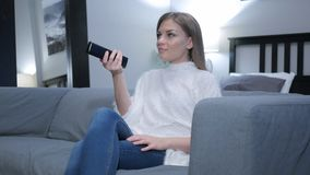 Kobieta Ogląda TV, Zmienia kanały z pilotem zdjęcie stock