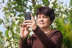 Kobieta ono fotografuje przeciw kwitnąć jabłka zdjęcie royalty free