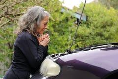 Kobieta ono modli się nad jej samochodem fotografia stock