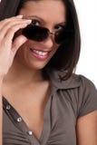 Kobieta ono przygląda się nad okularami przeciwsłoneczne Zdjęcie Royalty Free
