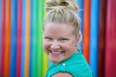 Kobieta ono uśmiecha się kolorową ścianą Obrazy Stock