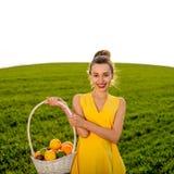 Kobieta ono uśmiecha się na greenfield z koszem owoc zdjęcia stock
