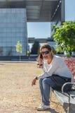 Kobieta ono uśmiecha się podczas gdy opowiadający na telefonie komórkowym, siedzi na ławce w parku obraz royalty free