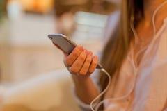 Kobieta opiera na prętowym wysylanie sms z jej motłochem i kontuarze Obraz Royalty Free