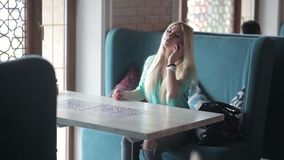 Kobieta opowiada na czekaniach dla stołu i telefonie zdjęcie wideo