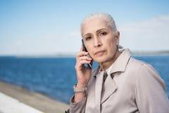 Kobieta opowiada na smartphone i patrzeje kamerę przy quay Fotografia Royalty Free