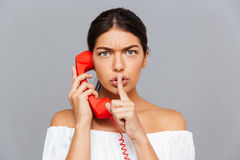Kobieta opowiada na telefon tubce i pokazuje cisza gest fotografia royalty free