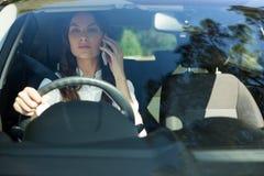 Kobieta opowiada na telefonie komórkowym podczas gdy jadący samochód obrazy royalty free