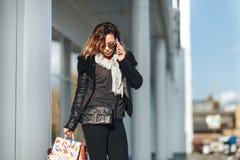 Kobieta opowiada na telefonie komórkowym przed odzwierciedlającymi okno o w słońc szkłach czarna skórzana kurtka, czarni cajgi z  Fotografia Royalty Free