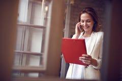 Kobieta opowiada na telefonie komórkowym z pracownikiem w studiu Fotografia Royalty Free