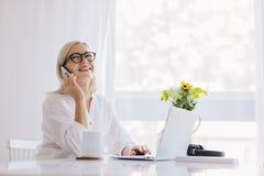Kobieta opowiada na telefonie laptopem obrazy royalty free