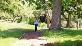 Kobieta opowiada na telefonie podczas gdy chodzący zbiory