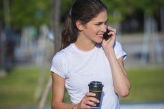 Kobieta opowiada na telefonie trzyma napój przy parkiem Zdjęcia Stock