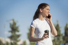 Kobieta opowiada na telefonie trzyma napój przy parkiem Zdjęcie Stock