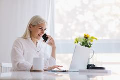Kobieta opowiada na telefonie, używać laptop obraz royalty free