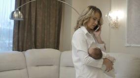 Kobieta opowiada na telefonie z dzieckiem w ona ręki zdjęcie wideo