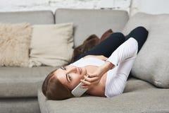 Kobieta opowiada na telefonu komórkowego lying on the beach na leżance Fotografia Stock