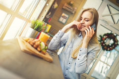 Kobieta opowiada o coś na telefonie komórkowym podczas gdy siedzący przy stołem w wygodnej Bożenarodzeniowej kawiarni Zdjęcie Stock