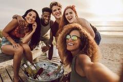Kobieta opowiada selfie z przyjaciółmi przy wyrzucać na brzeg przyjęcia obraz stock