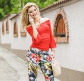 Kobieta opowiada telefonem outdoors w miasto ulicie Portret młoda uśmiechnięta mody dziewczyny pozycja z telefonem obraz stock