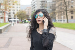 Kobieta opowiada telefonem w ulicie z okularami przeciwsłonecznymi Zdjęcia Royalty Free