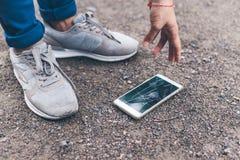 Kobieta opuszczał telefon komórkowego na ziemi i roztrzaskiwał ekran fotografia royalty free
