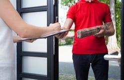 Kobieta otrzymywa pakunek od doręczeniowego mężczyzna zdjęcia royalty free
