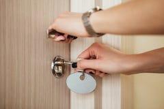 Kobieta otwiera drzwi z kluczem W górę ręk i keyhole obraz royalty free