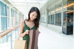 Kobieta otwiera papierową torbę w zakupy centrum handlowym Fotografia Royalty Free