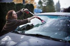 Kobieta outside przeznaczać do rozbiórki mróz jej przednia szyba w zimie Obrazy Stock