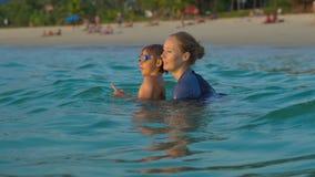 Kobieta pływacki instruktor uczy chłopiec dopłynięcie w morzu podczas sundet zdjęcie wideo