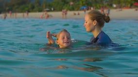 Kobieta pływacki instruktor uczy chłopiec dopłynięcie w morzu podczas sundet zbiory