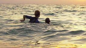 Kobieta pływacki instruktor uczy chłopiec dopłynięcie w morzu podczas sundet zbiory wideo