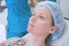 Kobieta pacjent w higienicznym kapeluszu oczekuje procedurę w doktorskim ` s biurze Zakończenie 4K Zdjęcia Stock