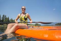 Kobieta paddleboarding na scenicznym jeziornym niskiego kąta widoku Obrazy Stock