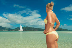 Kobieta patrzeje łódź morzem z rękami na jej talii zdjęcie royalty free