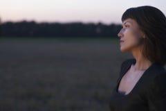 Kobieta Patrzeje Daleko od W polu Przy zmierzchem Fotografia Stock
