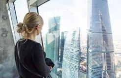 Kobieta patrzeje drapacze chmur Dopatrywanie pejzaż miejski od drapacza chmur wnętrza Obrazy Stock