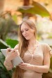 Kobieta patrzeje jej pastylkę Zdjęcie Stock