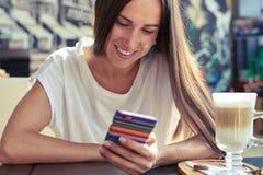 Kobieta patrzeje jej smartphone Zdjęcie Stock