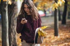 Kobieta patrzeje jej telefonu komórkowego smartphone w ręce w jesieni outdoors Zdziwiona dziewczyna w spadku lesie fotografia stock