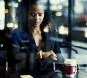 Kobieta patrzeje jej zegarek przy kawiarnią zdjęcia royalty free